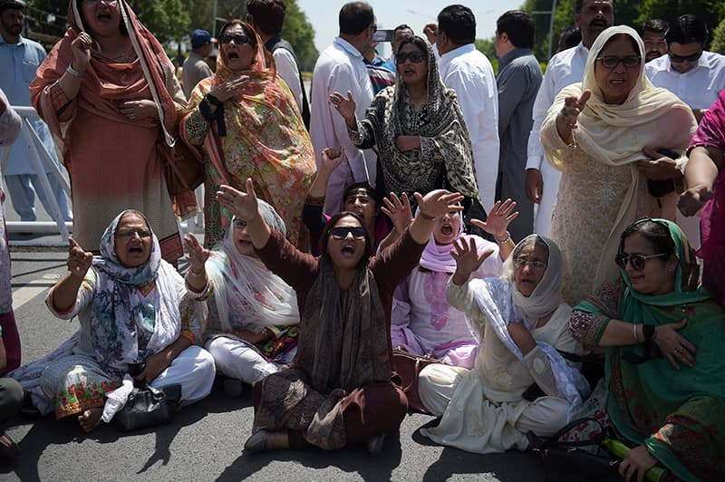 Supporters of the ruling PML-N shout slogans against the SC verdict. — AFP