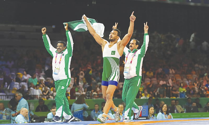 GOLD COAST: Pakistan's Mohammad Inam Butt (C) takes a victory lap with his coaches after winning in the men's freestyle 86Kg wrestling finals against Nigeria's Melvin Bibofinals at the Commonwealth Games on Saturday.—AP