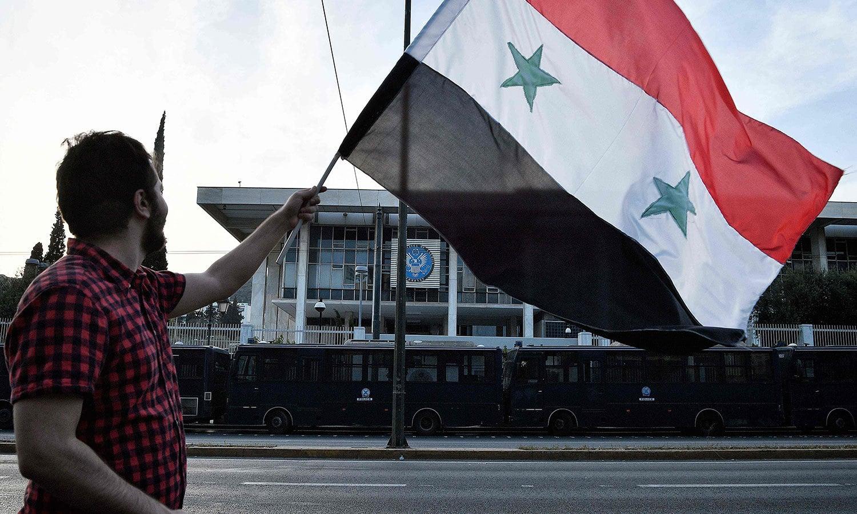 ایتھنز میں مظاہرین نے شام کا پرچم اٹھایا ہوا تھا—فوٹو: اے ایف پی