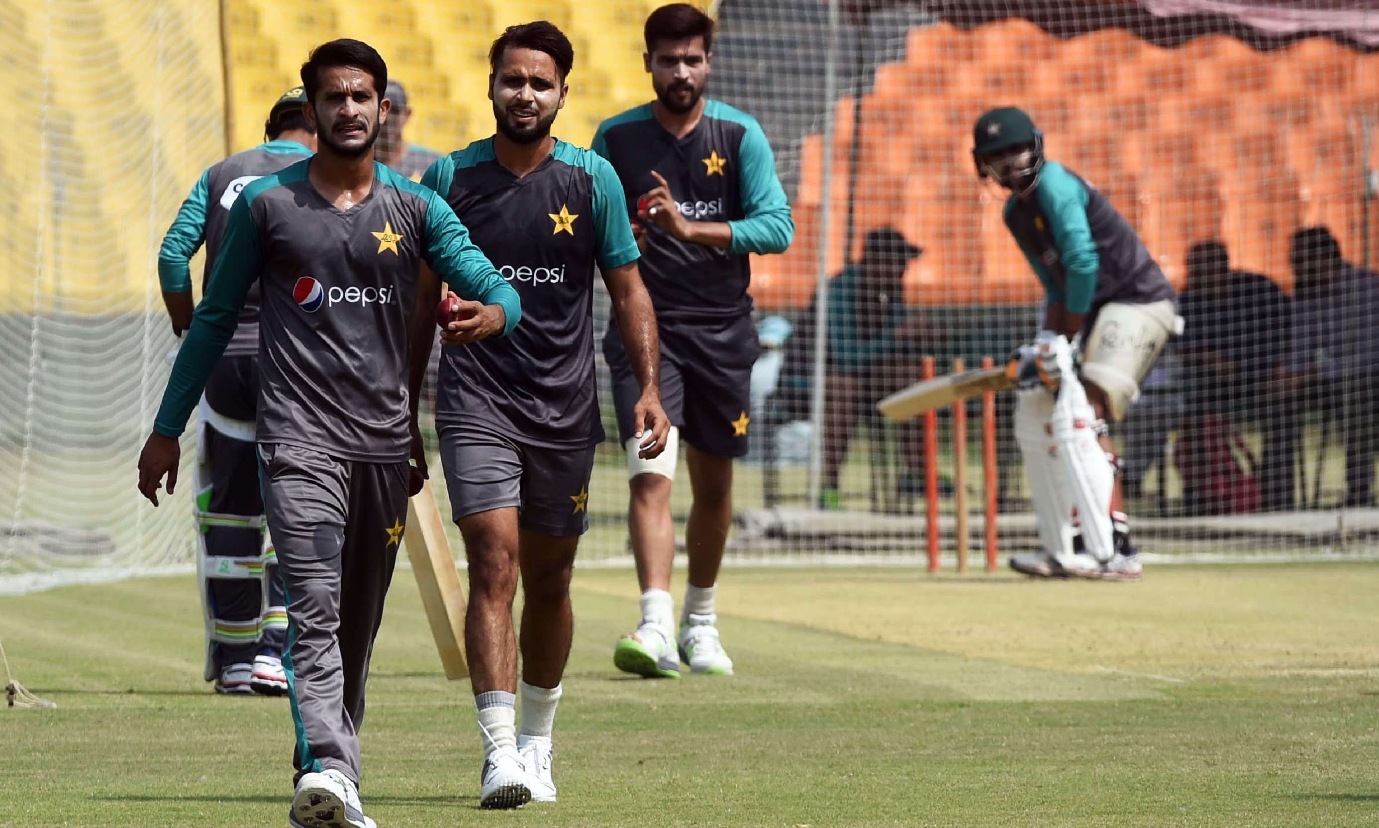 Mohammad Amir, Hassan Ali and Faheem Ashraf walk after delivering a ball during a practice session in Lahore. —AFP
