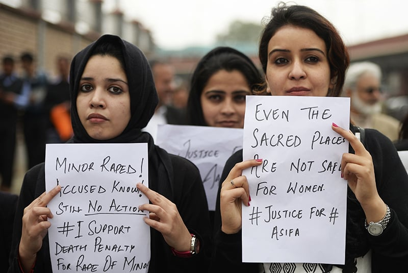 Kashmiri lawyers hold placards during a protest calling for justice, in Srinagar. — AFP