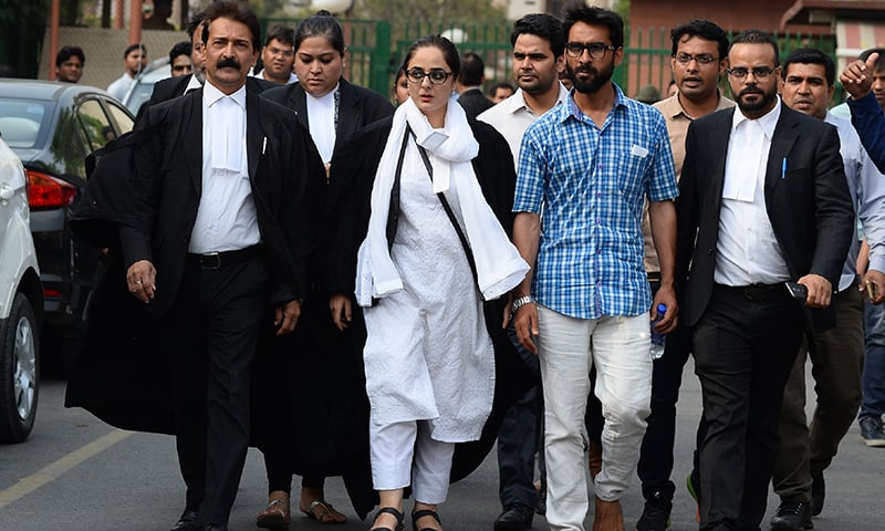 Indian lawyer Deepika Singh Rajawat (C), counsel for the family of a young girl who was raped and murdered, walks outside the Supreme Court to address the media in New Delhi on Monday. — AFP