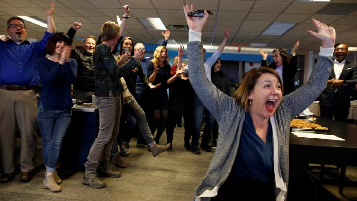 Amber Hunt, reporter Cincinnati Enquirer (R) and other journalists in the Enquirer newsroom celebrate as they learn of winning a Pulitzer Prize for local reporting