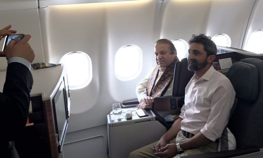 PML-N leader Nawaz poses for a picture with a fellow passenger on his flight to London. — Photo courtesy Maryam Nawaz's Twitter account