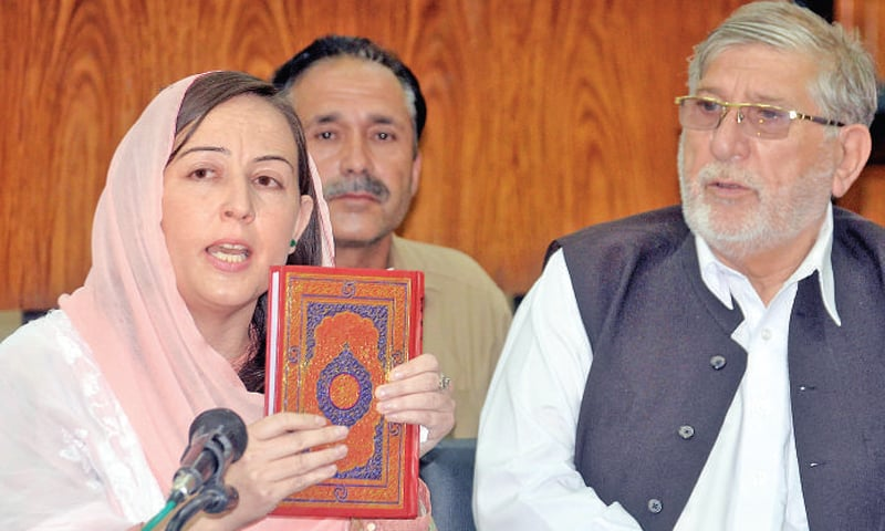PTI lawmaker Fozia Bibi holds the holy Quran while addressing a press conference in Peshawar on Thursday. — White Star