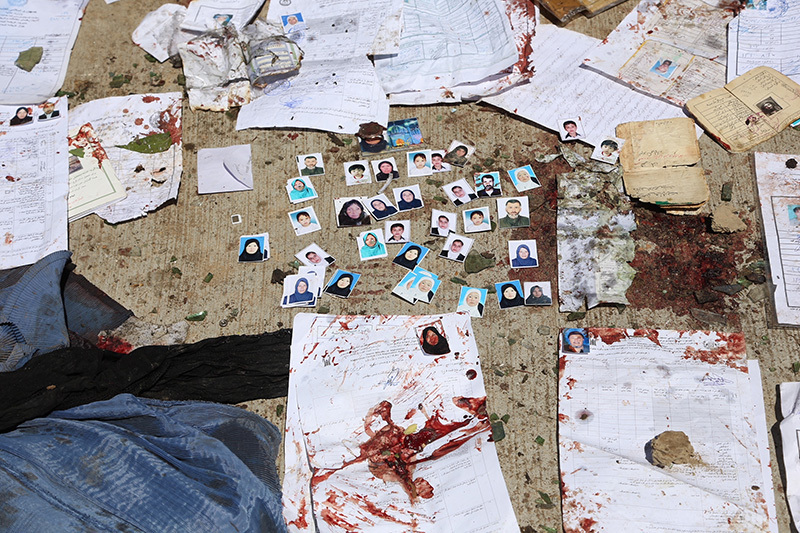 Blood-stained National ID papers and voters' photos are seen on the ground after the suicide attack. — AP