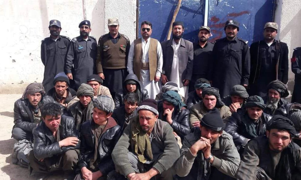 Afghan illegal migrants, several of them Uzbek, arrested by the Levies force. Some Levies personnel can be seen standing in the background. — Dawn