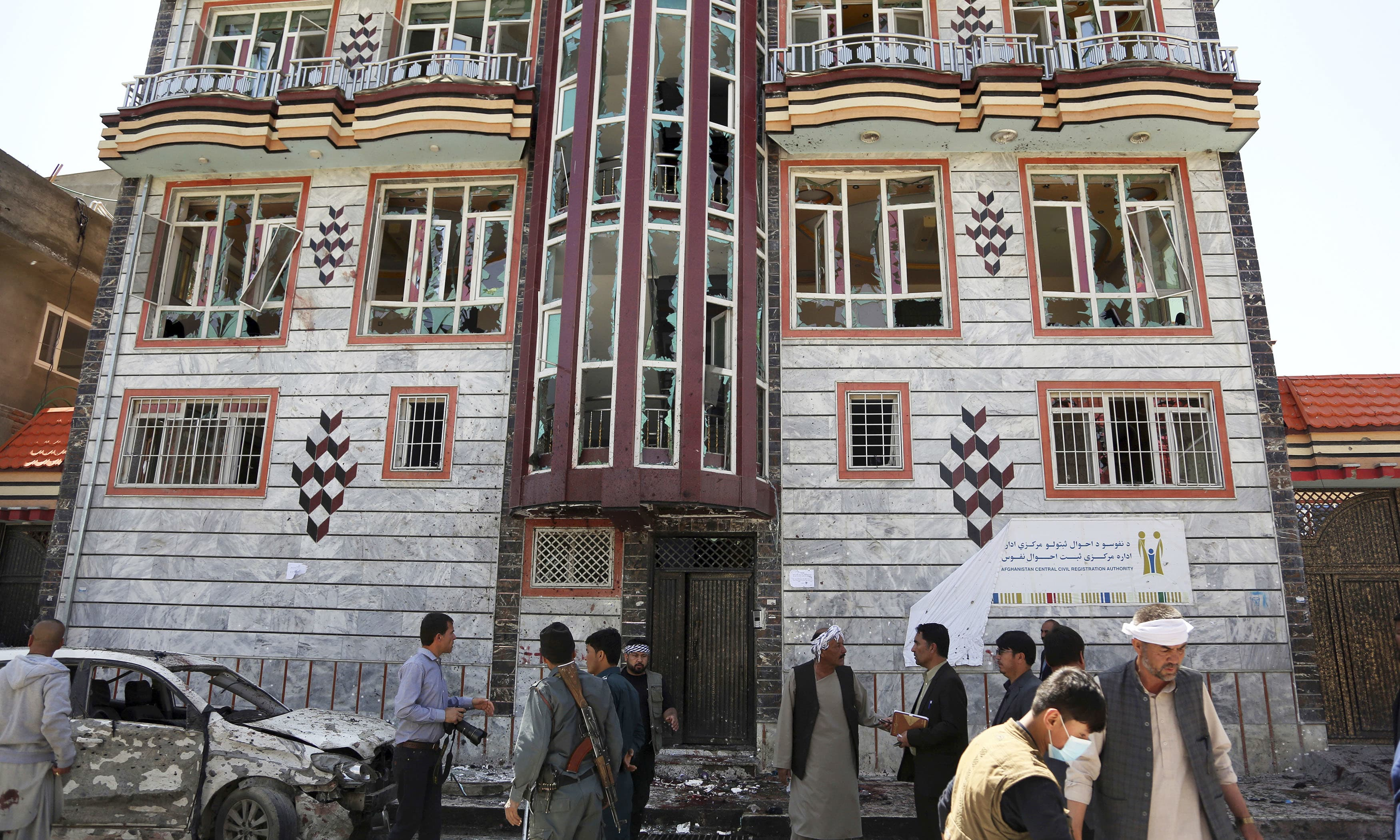 People gather outside a voter registration centre which was attacked by a suicide bomber in Kabul. —AP