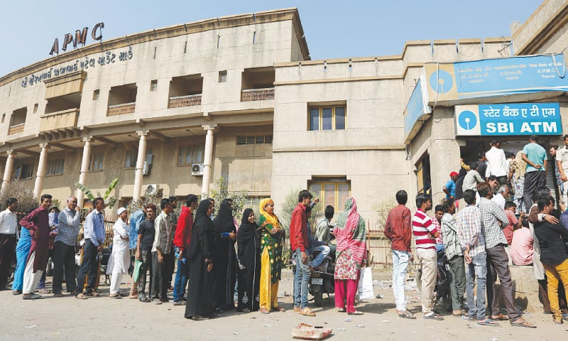 Indians stand in a queue outside a bank to withdraw cash in Ahmadabad, India. Roughly seven out of every 10 adults worldwide now has some form of a bank account, the World Bank said last Thursday, fueled largely by the proliferation of cell phone-based bank accounts and other simple bank account programs in places like India and Sub-Saharan Africa.—AP