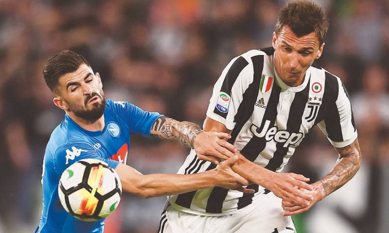 NAPOLI'S Elseid Hysaj (L) fights for the ball with Juventus' Mario Mandzukic.—AFP
