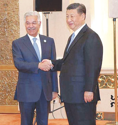 FOREIGN Minister Khawaja Asif shakes hands with Chinese President Xi Jinping before a meeting at the Great Hall of the People on Monday.—APP