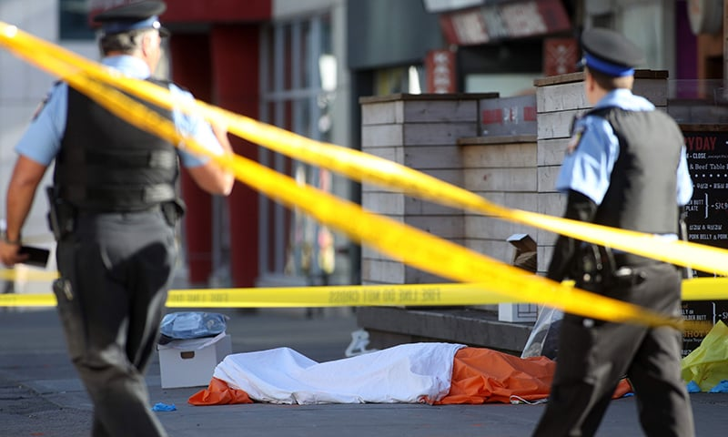 Police officers stand near one of the bodies on the street after a truck drove up on the curb and hit several pedestrians in Toronto. — AFP