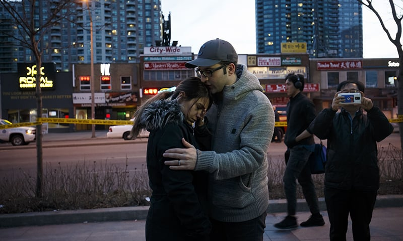 People embrace at the scene of a memorial for victims of a crash at Yonge St. at Finch Ave., after a van plowed into pedestrians on April 23 in Toronto, Canada. — AFP