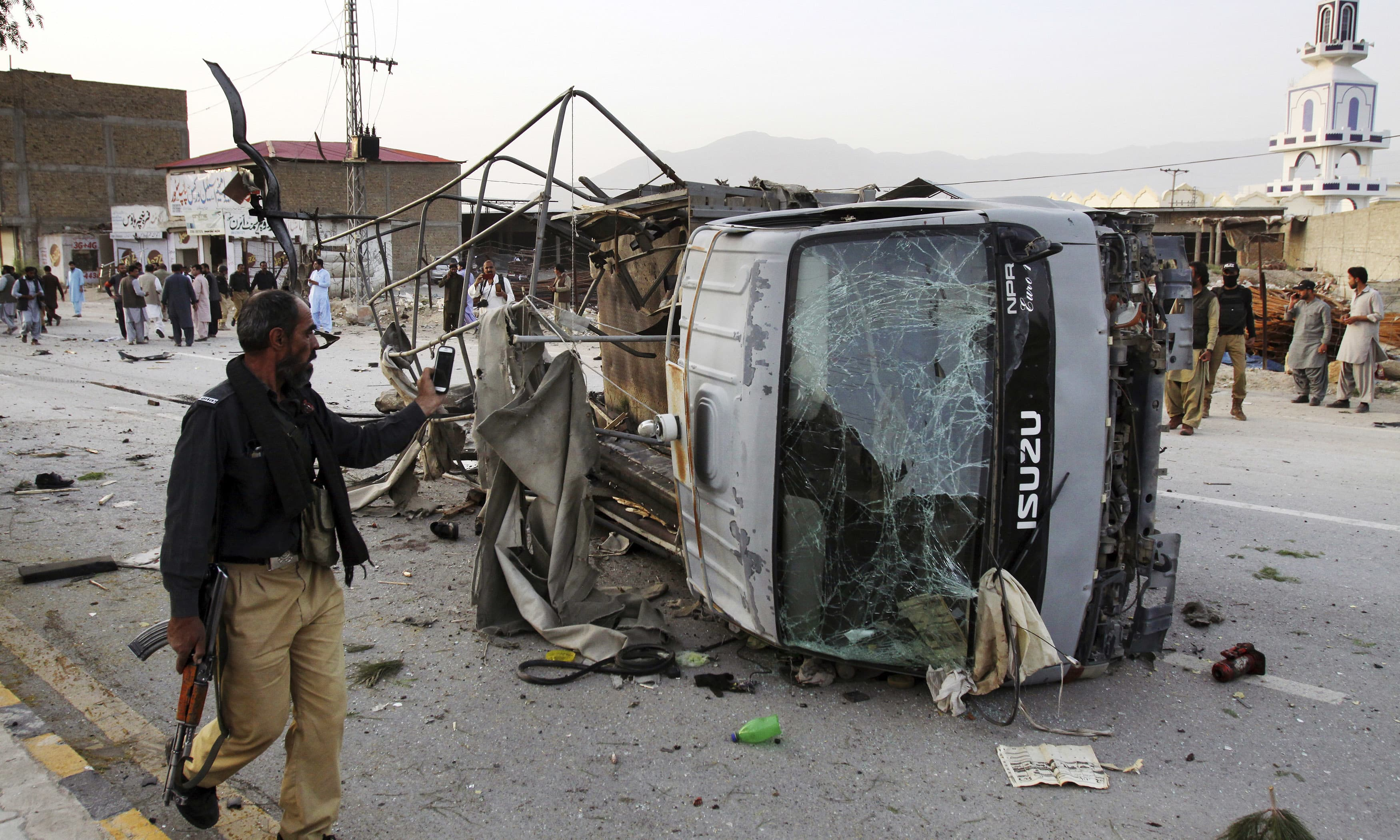 Policeman walks past the vehicle targeted by suicide bomber. —AP