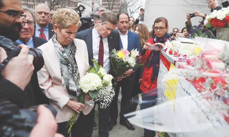 ONTARIO Prime Minister Kathleen Wynne and Toronto Mayor John Tory bring flowers to the makeshift memorial for victims of the attack.—AFP