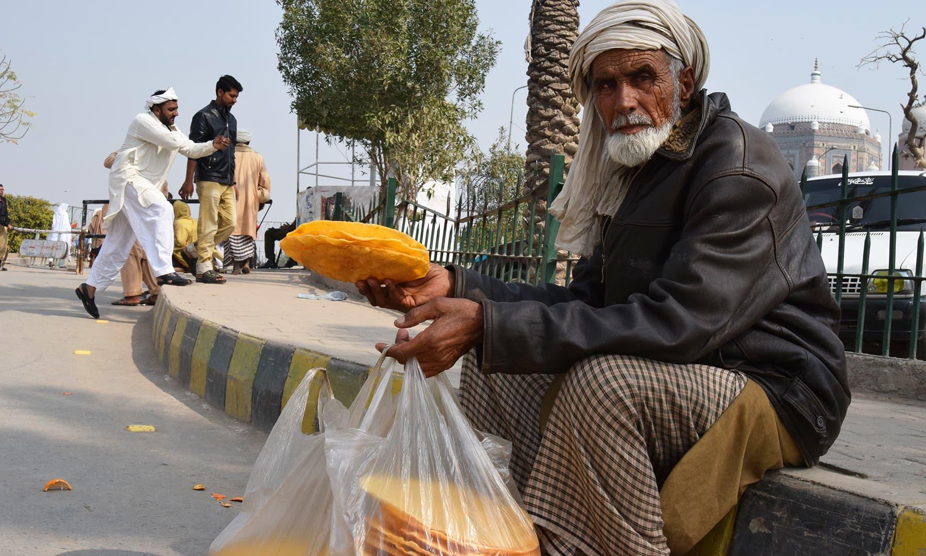عمر رسیدہ محمد شفیع اپنے نافرمان نشئی بیٹے کی وجہ سے عمر کے اس حصے میں بھی منتف مزدوری کرنے پر مجبور ہیں—تصویر عظمت اکبر