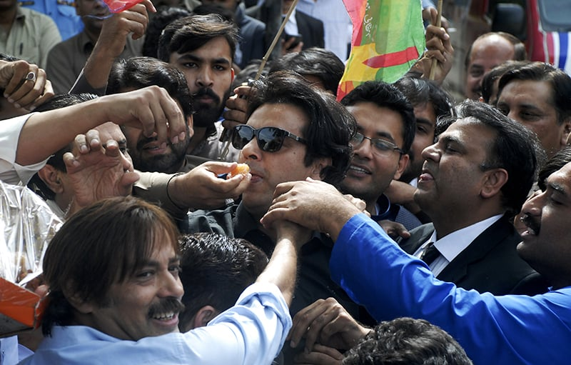 PTI supporters offer sweets to Usman Dar, centre, who filed the petition against Khawaja Asif after the verdict was announced. — AP