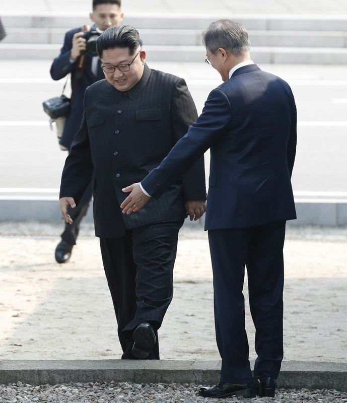 Kim Jong Un, left, crosses the military demarcation line to meet with Moon Jae-in, right, at the border village of Panmunjom in the Demilitarized Zone on Friday. ─ AP
