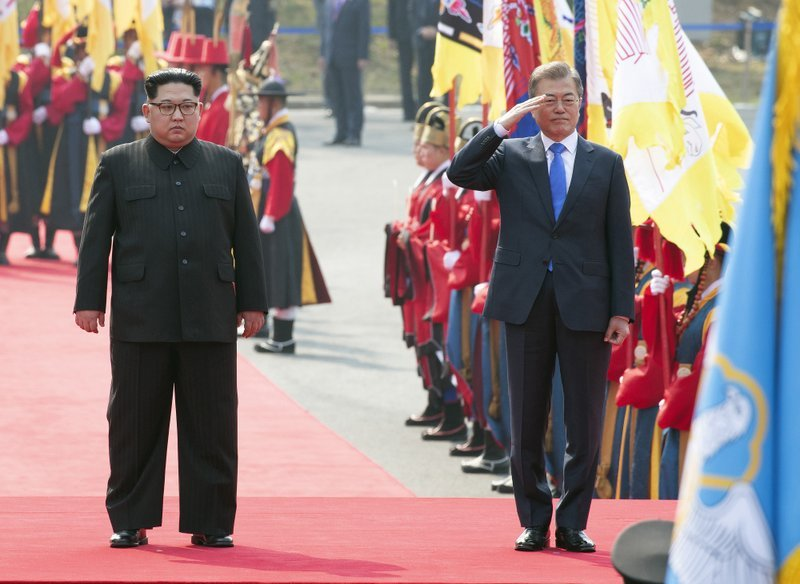 Kim Jong Un, left, and Moon Jae-in inspect honor guard as Kim crossed the border into South Korea for their historic face-to-face talks, in Panmunjom on Friday. ─ AP