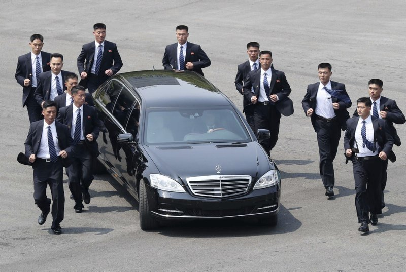 North Korean security persons run by the car carrying North Korean leader Kim Jong Un. ─ AP