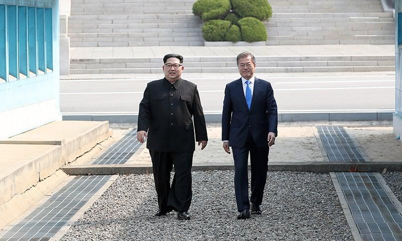 جنوبی کوریا کے صدر مون جے اِن (دائیں) اور شمالی کوریا کے لیڈر کِم جونگ اُن (بائیں) ڈیمارکیشن لائن پر جنوبی کوریا میں داخل ہورہے ہیں — فوٹو، اے ایف پی