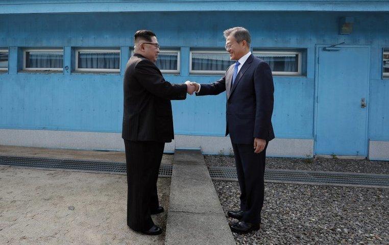جنوبی کوریا کے صدر مون جے اِن (دائیں) اور شمالی کوریا کے لیڈر کِم جونگ اُن (بائیں) ڈیمارکیشن لائن پر مصافحہ کر رہے ہیں — فوٹو، اے پی