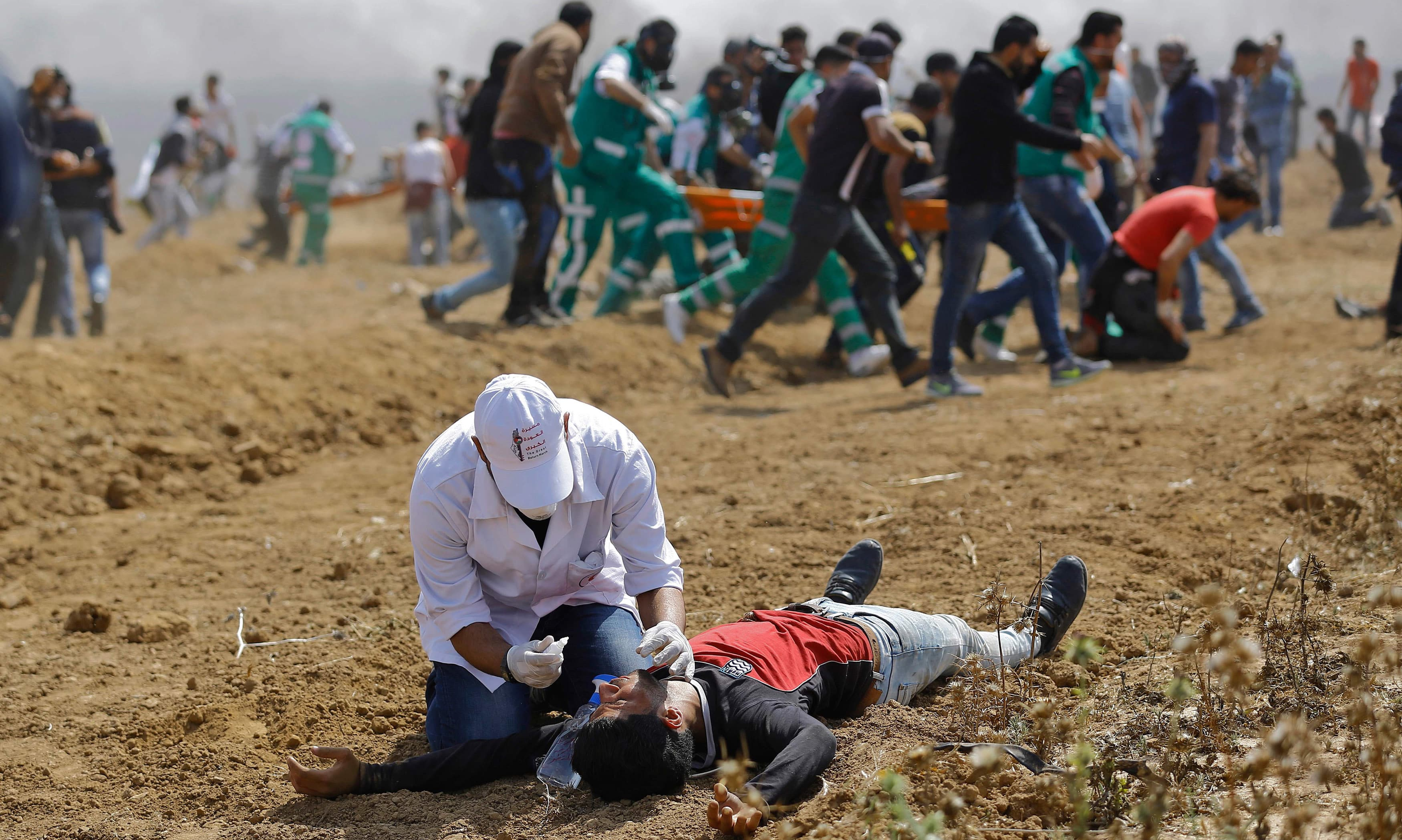A Palestinian helps a man during clashes with Israeli security forces near the eastern border of the Gaza Strip. —AFP