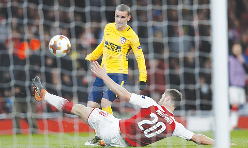 LONDON: Atletico Madrid's Antoine Griezmann shoots past Arsenal's Shkodran Mustafi to score during the Europa League semi-final first leg at the Emirates Stadium.—AFP