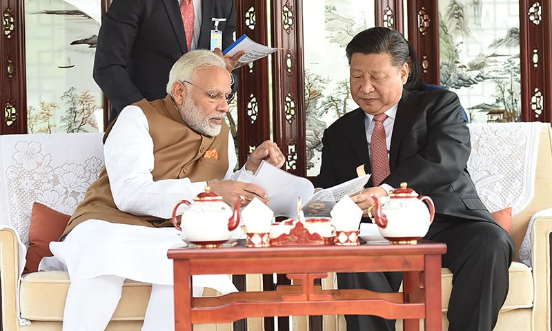 This photograph released by India's Press Information Bureau (PIB) shows India's Prime Minister Narendra Modi (L) and Chinese President Xi Jinping looking on in a house boat, at East Lake, in Wuhan. — AFP