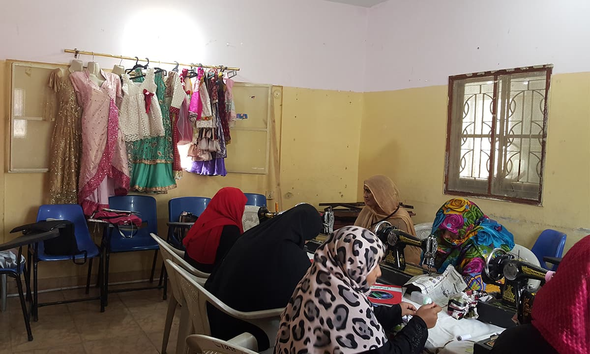 Bright clothes made by students are displayed while the women are busy in their sewing class — some start their own businesses once their course is complete | Photo by Sarah Dara