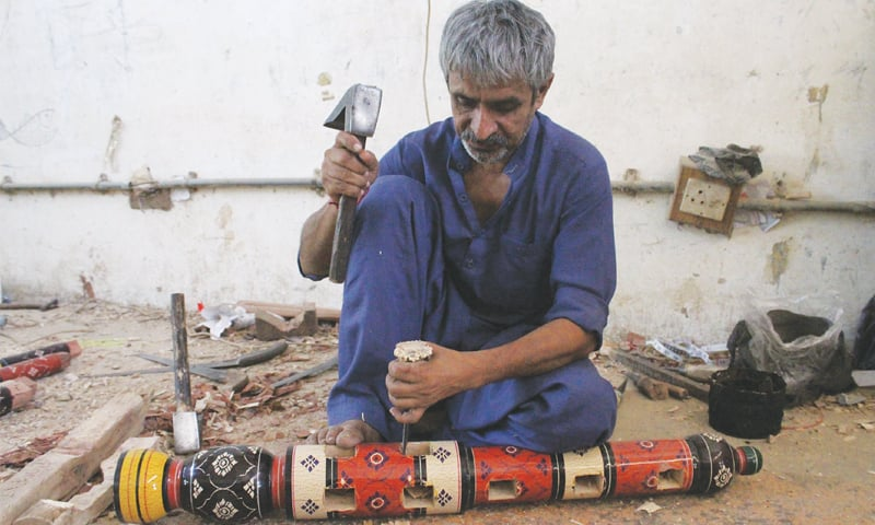 A craftsman makes holes to join different pieces of the hindoro together