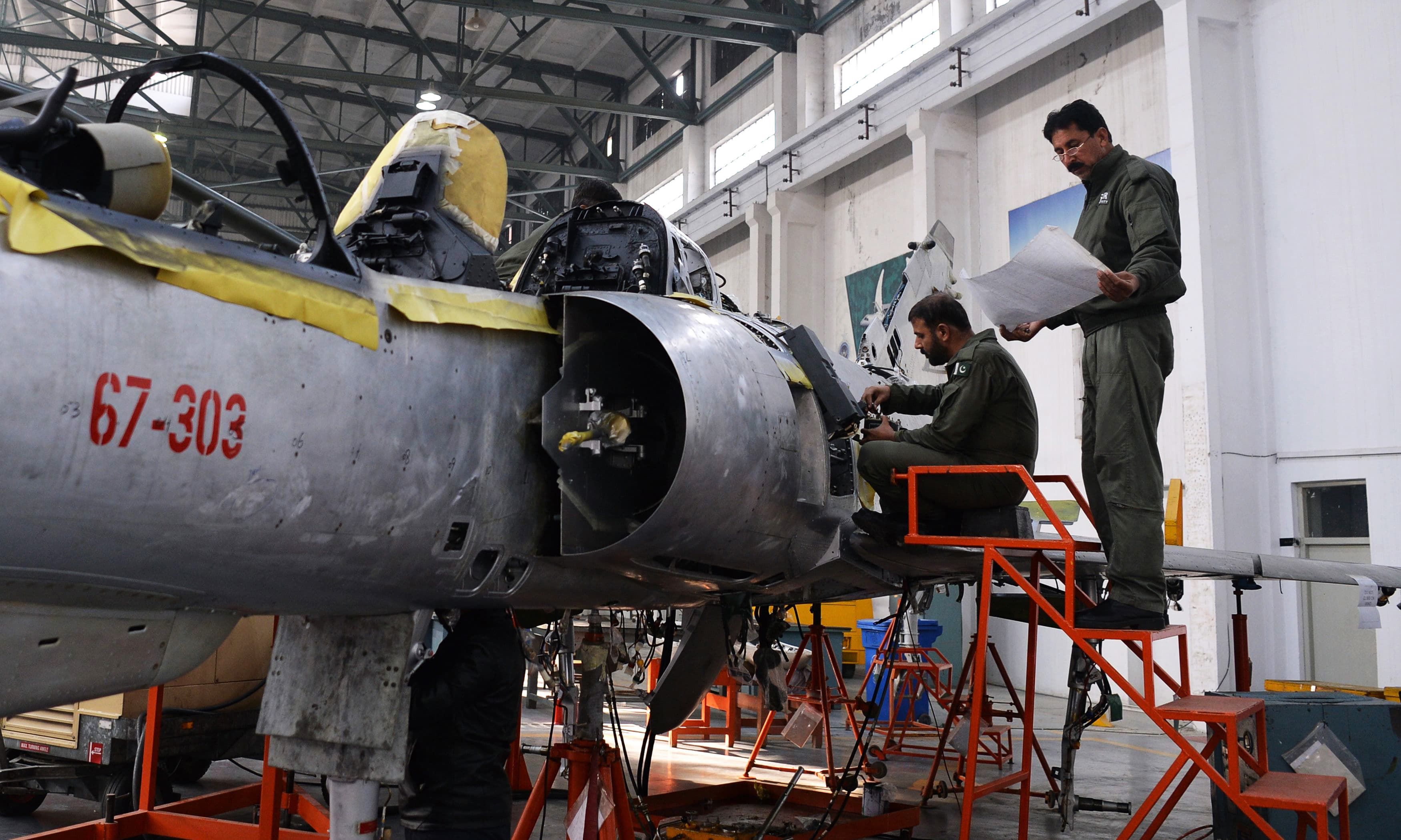 Technicians work on a Mirage aircraft during a full overhaul by the PAF. — AFP