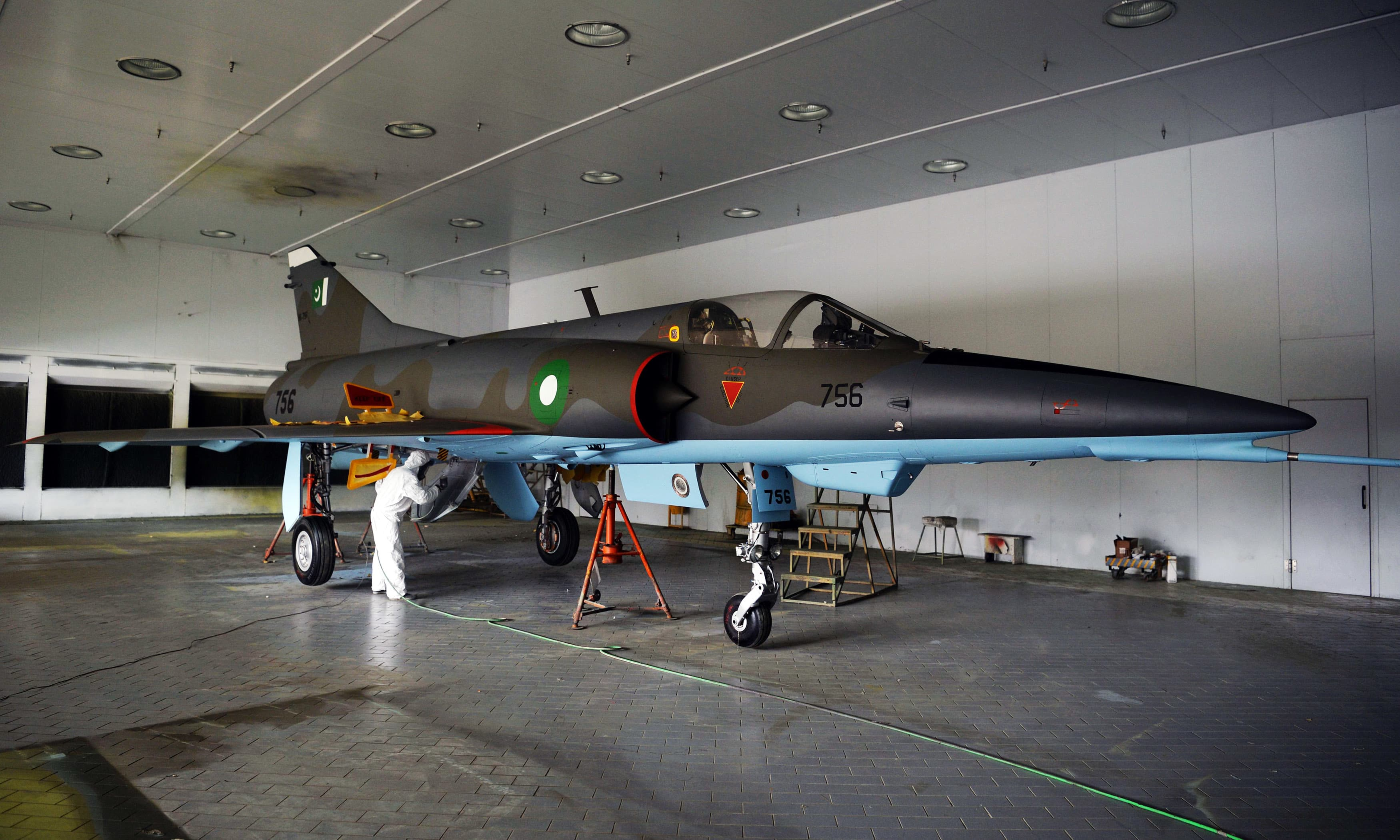 Technicians paint a Mirage aircraft after being serviced by at the Mirage Rebuild Factory in Kamra. —AFP