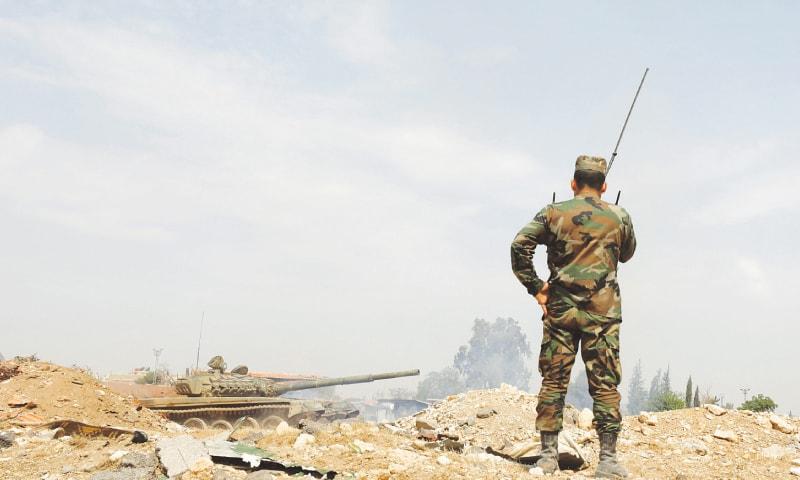 DAMASCUS: Soldiers loyal to Syrian President Bashar al-Assad are deployed at al-Qadam area near Yarmouk Palestinian camp on Sunday.—Reuters