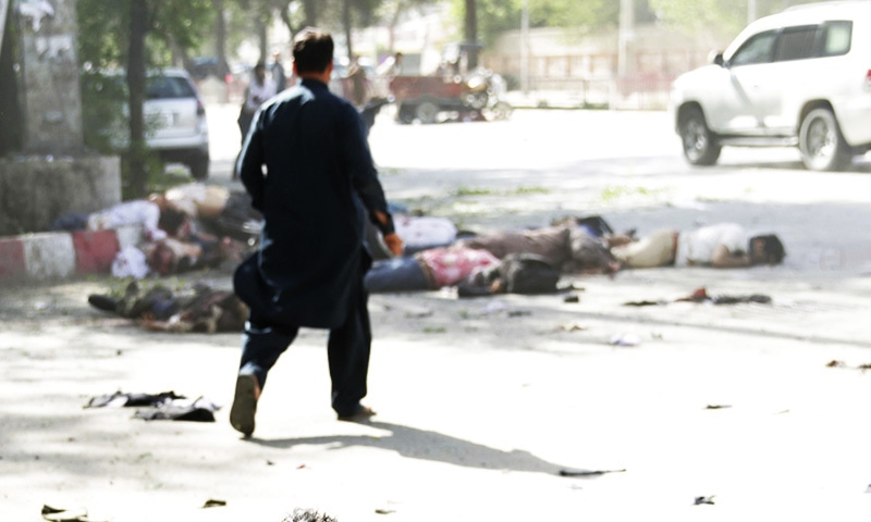 A wounded man looks at the site of double explosions, in Kabul. — AP