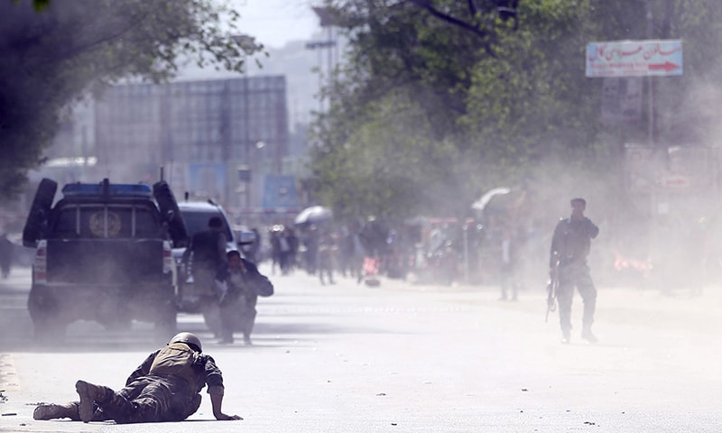 A security force official and a civilian lie low at the site of a suicide attack after the second bombing in Kabul. — AP
