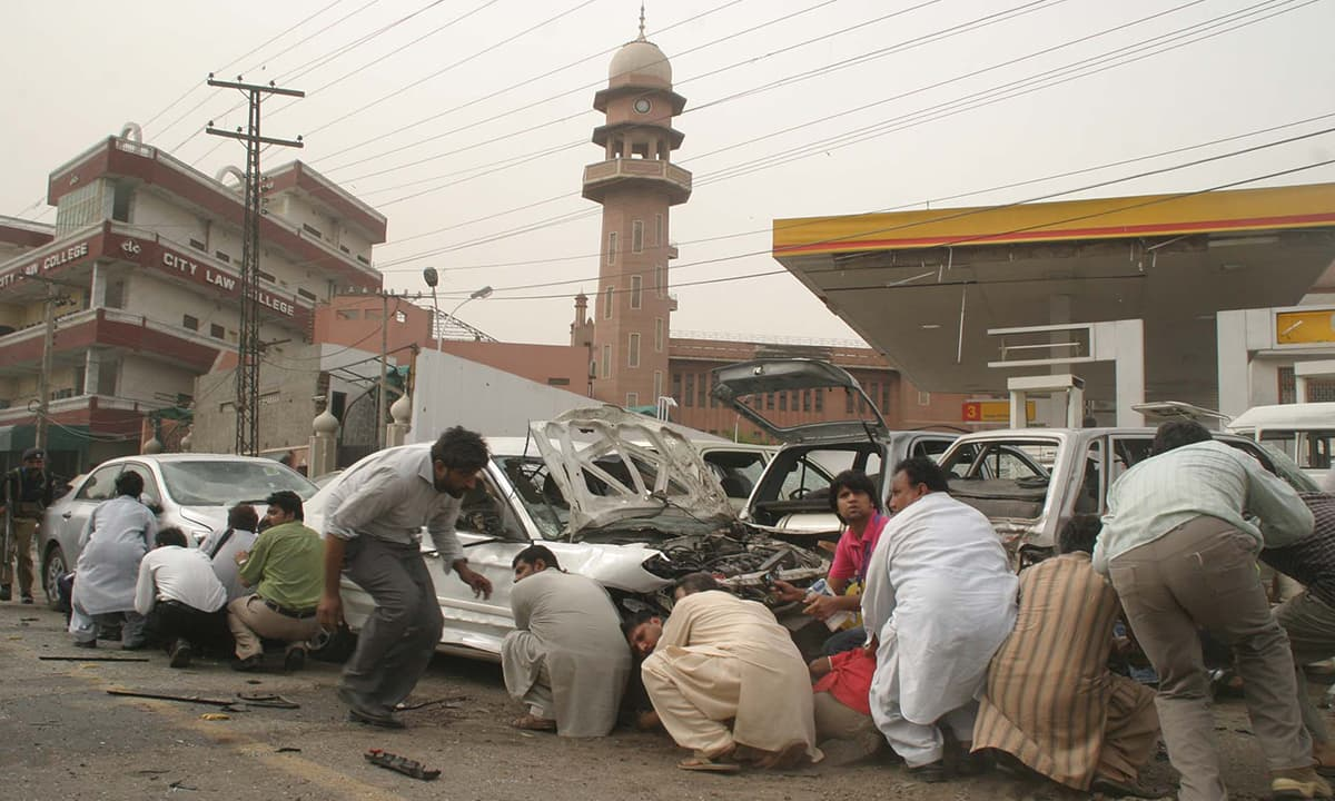 People duck for safety as terrorists take hold of an Ahmadi prayer hall in Lahore in 2010 | M Arif, White Star