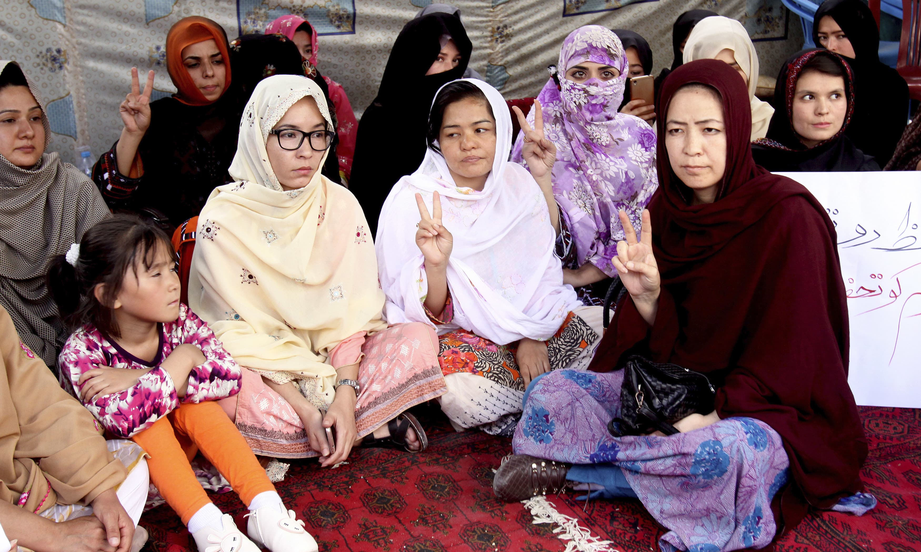 Hazara women participate in a hunger strike at a camp outside press club in Quetta. —AP