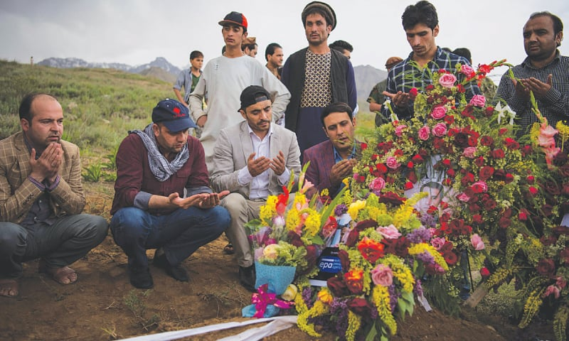 KABUL: Friends and relatives of AFP Afghanistan Chief Photographer Shah Marai Faizi gather at his burial site in Gul Dara after his death in the second of two bombings that occurred in the Afghan capital.—AFP
