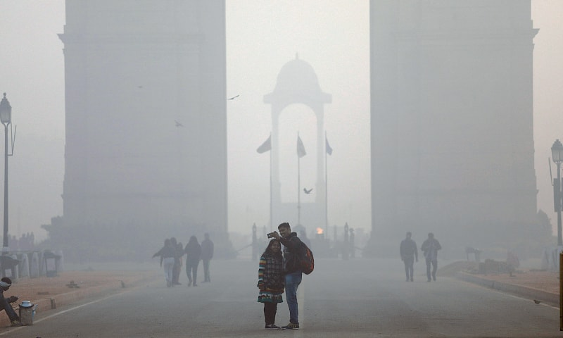 Two youngsters take a selfie in front of the India Gate on a smoggy morning in New Delhi.—Reuters