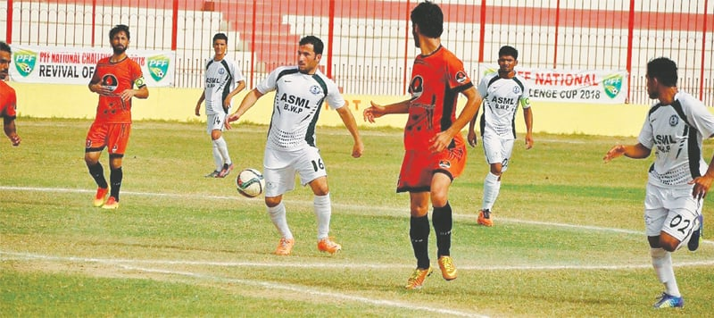 PLAYERS of Ashraf Sugar Mills and Pakistan Petroleum Limited vie for the ball  during the National Challenge Cup quarter-final at the KPT Football Stadium on Thursday.—Courtesy PFF