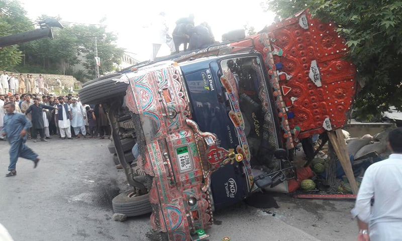 An Abbottabad-bound truck loaded with wheat bags overturned on a Mansehra-bound van in Abbottabad. —Photo provided by author