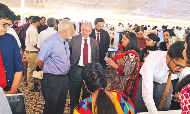 Vice Chancellor Air University Faaiz Amir and chief guest Imtiaz Ali Rastgar visiting the open house stalls. — Dawn