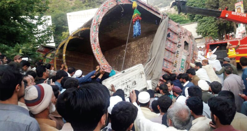 People push a truck that overturned on a passenger van in Abbottabad on Thursday.—Dawn