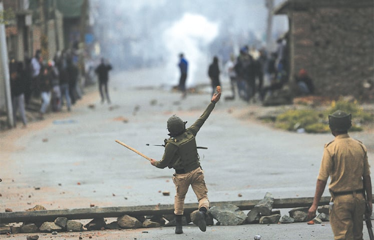A POLICEMAN hurls a stone at protesters in Srinagar.—AP