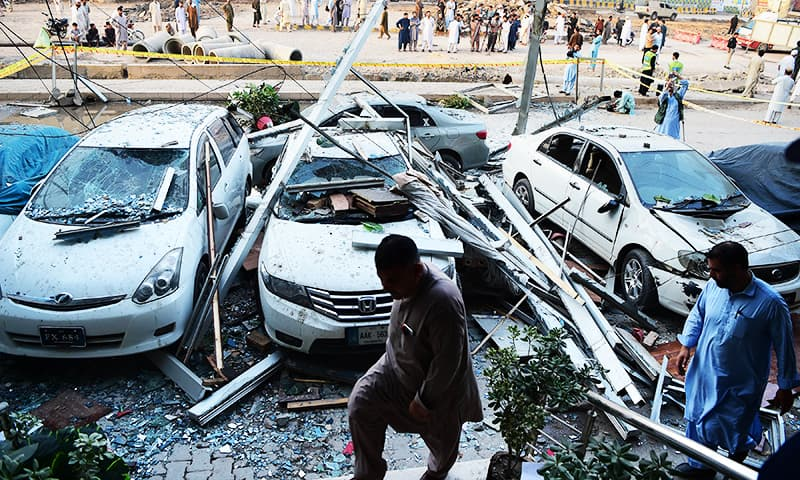 Plain-clothed police officials walk past damaged vehicles following a gas explosion.— AFP