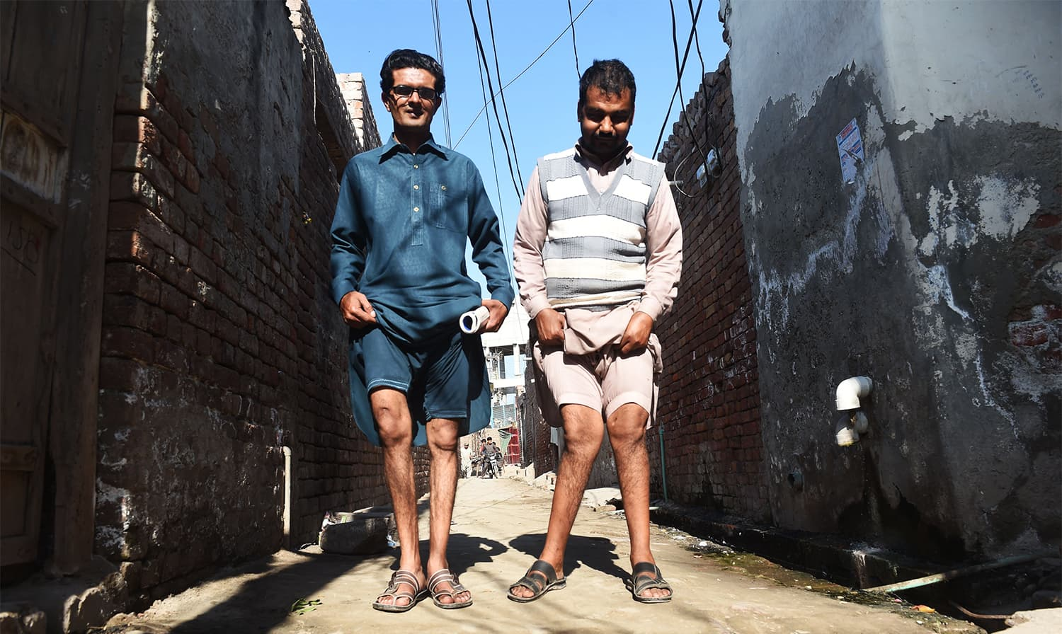 In this picture taken on February 25, 2018, Basharat Ali (L) and Naveed show their deformed lags allegedly caused by environmental factors and polluted groundwater in Kot Assadullah, around 45km from Lahore. ─ AFP