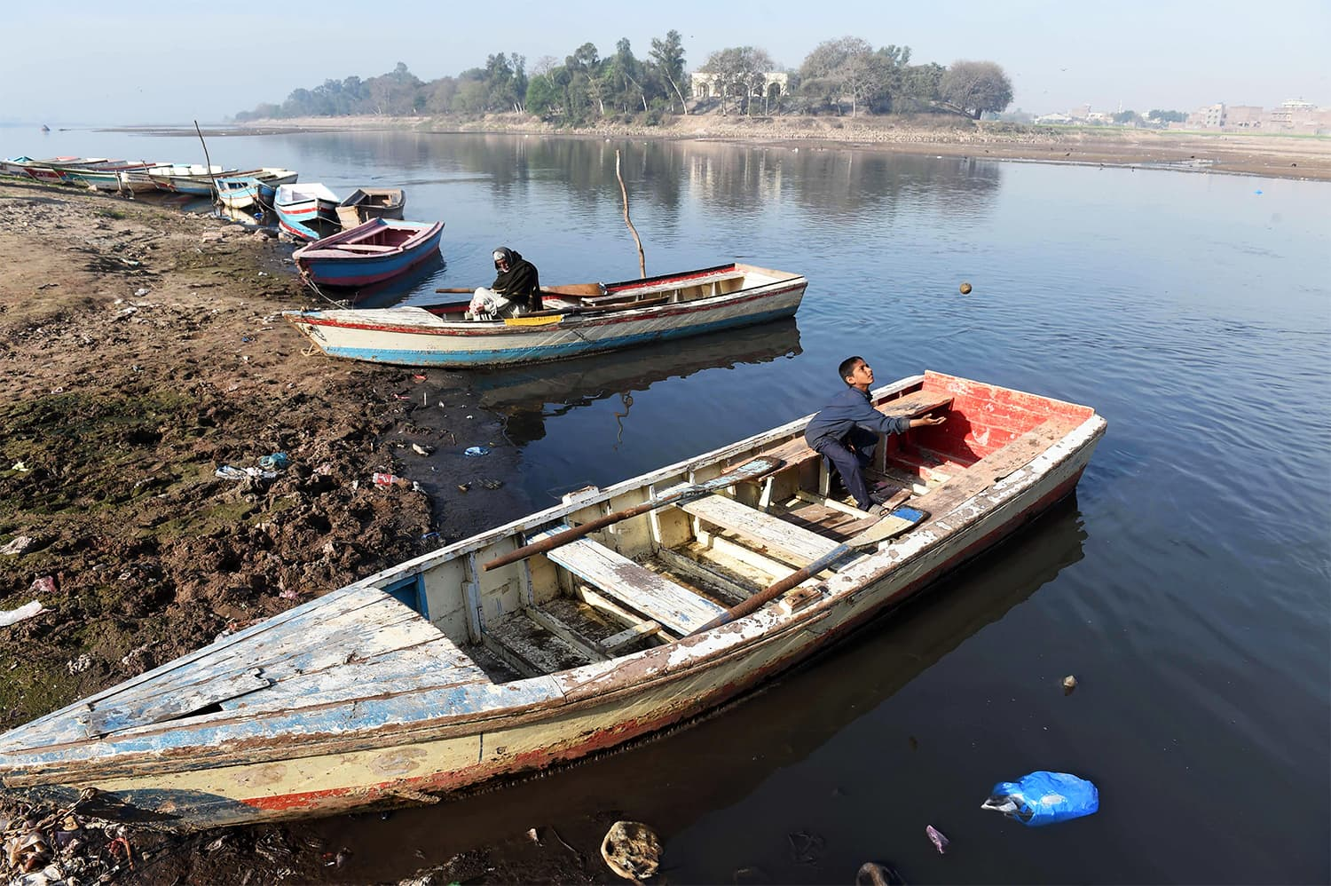 A young boy playing in a boat moored in the polluted Ravi river on the outskirts of Lahore. ─ AFP