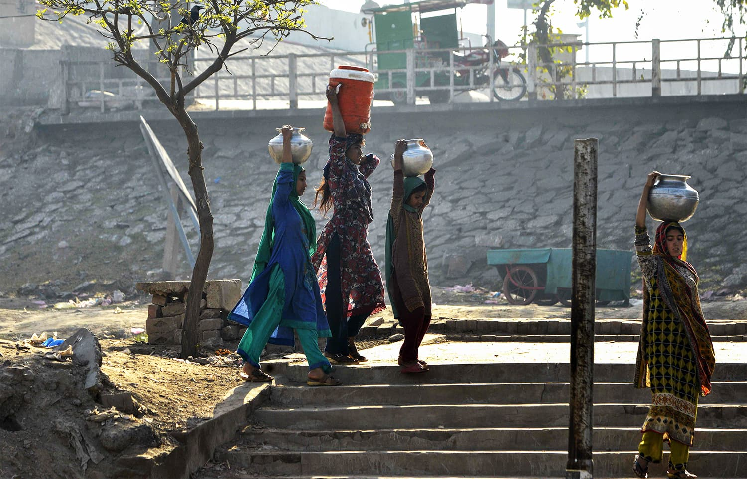 In this picture taken on February 26, 2018, shows residents carrying pots filled with drinking water from a handpump on the outskirts of Lahore. ─ AFP