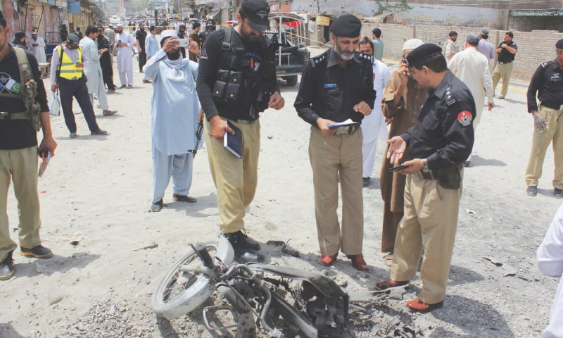BANNU: Police officials examine wreckage of a motorbike damaged in the explosion on Friday.—AP